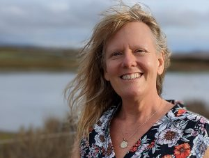 Janey Skinner, smiling with messy hair in a marsh