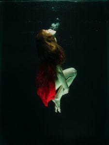 Woman underwater blowing bubbles